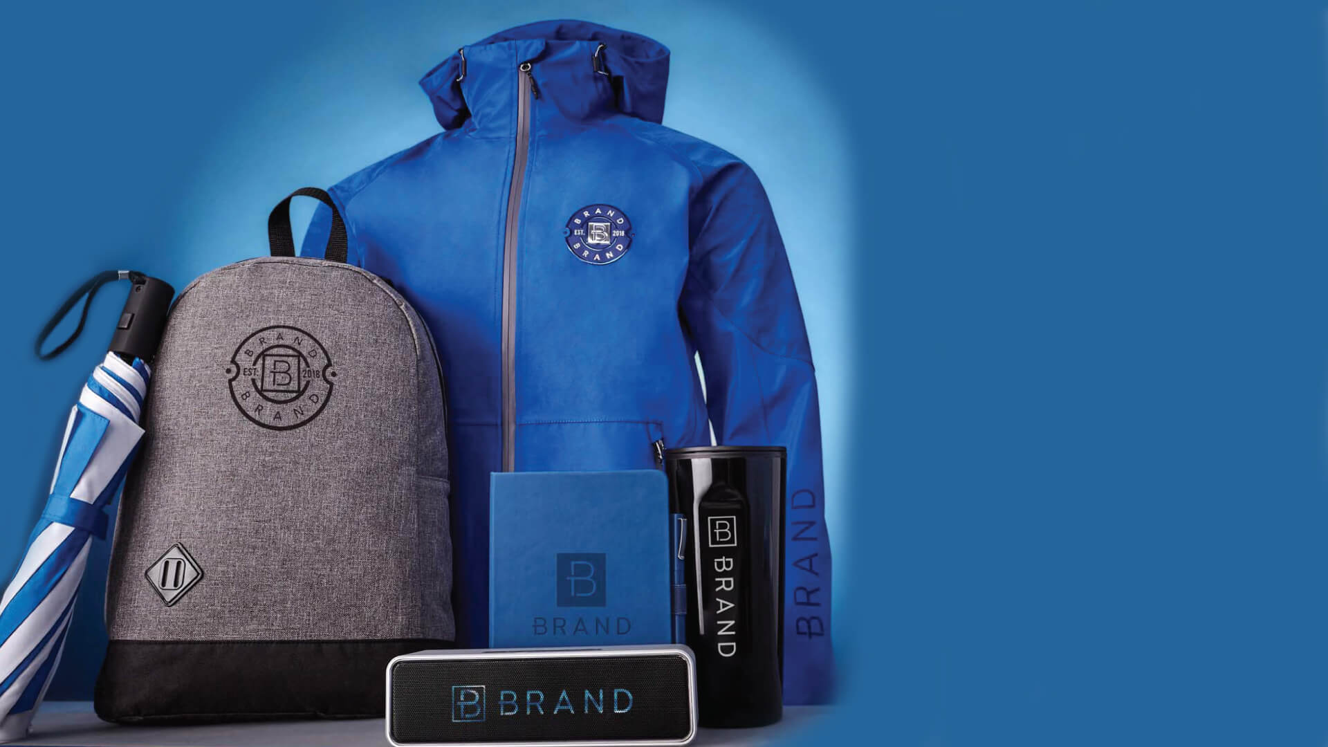 B brand gear with umbrella, jacket, notebook, cup, and speaker